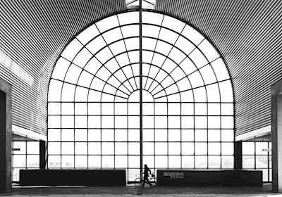 Calle Artmark - The Station II. A black and white photograph from a train station with a big arched window and a lone cyclist.