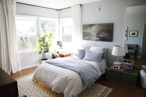 """""""Tall drapes accentuate the height of the room. Also, in large, bright rooms, painting the walls a lighter color allows the space to feel larger. If you want to create a more intimate feeling, painting the walls darker helps."""""""