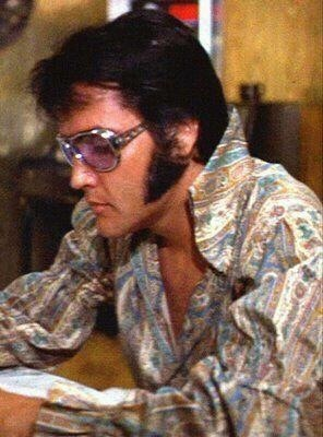 Elvis in dressing room reading telegrams before getting dressed for the opening night show at the International, August 10, 1970.