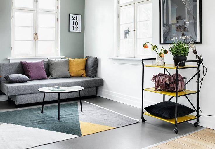 Stue med sofa-hjørne med gråt linoleumsgulv, grå sofa, farverige puder og rullebord med gule hylder