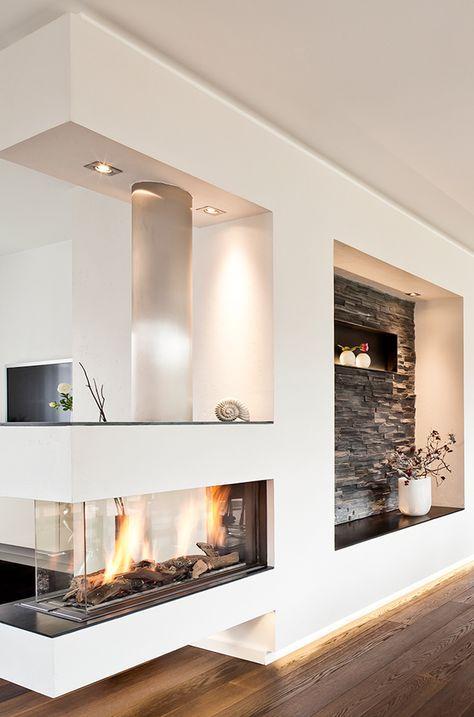 Wer braucht schon eine Wohnzimmerwand, wenn er einen so schönen Panorama Gaskamin mit moderner Steinvertäfelung und weißem Putz hat.