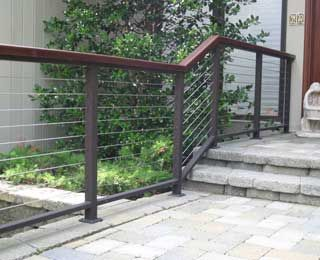"This Modern Cable Railing is fabricated with a 1"" by 2"" aluminum top and bottom bar bar with IPE wood top molding, 2"" square aluminum posts and 3/16"" stainless steel cables. The posts were mounted with 4"" square plates and secured to the paver blocks with fasteners. The railing flanks the main entrance to the clients home. CR-14"