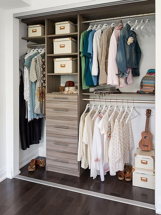 Condo closet features modular brown melamine shelving units and chest of drawers next to stacked clothes rails.
