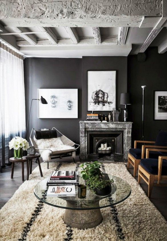 Black and white industrial loft space living room with Platner coffee table and sheepskin chair.