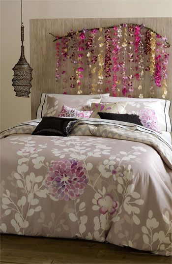 Such a whimsical bedroom. I'm loving the flowers strung above the bed and that gorgeous duvet.