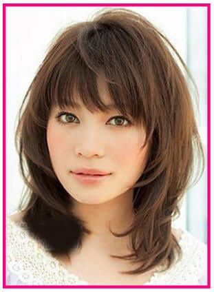 Medium Layered Haircut with Wispy Bangs and Light Inward Curl in Brown Hair Color for Oval Face