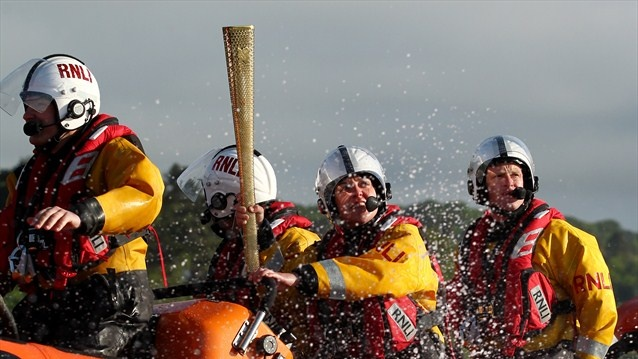The Beaumaris RNLI lifeboat crew assist Torchbearer Elen Evans as she carries the Olympic Flame across the Menai Strait on Day 11 of the London 2012 Olympic Torch Relay.