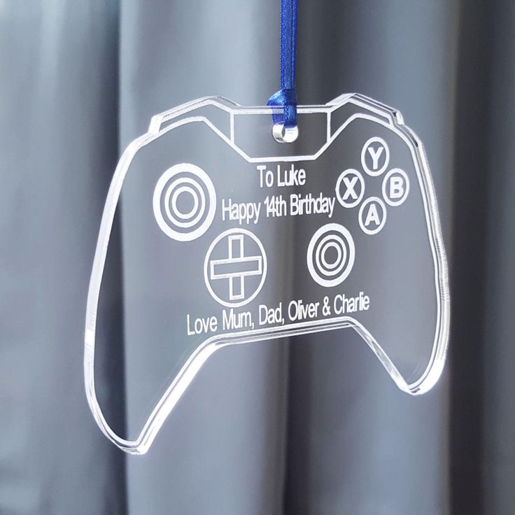 Personalised with a personal message at the top and bottom. Featuring an engraved game controller with all the buttons. The finished piece really catches the light. Made from high quality acrylic so its more durable than glass. Supplied with a length of royal blue ribbon so it is ready to hang. Approximate size: 85 x 95 x 5mm Price: £6.95