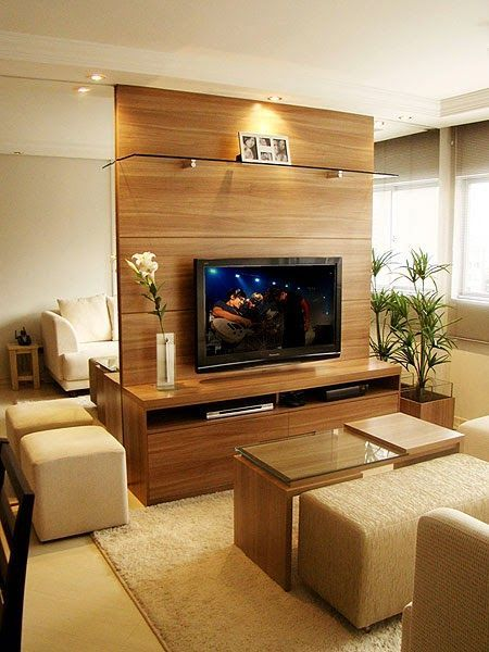 Sala de TV com painel de madeira e espelhos nas laterais.