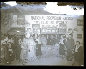 National Provision Stores booth at a bazaar held in the United Hebrew Temple at 225 South Skinker Boulevard. Signs advertise Anheuser-Busch root beer and Bouquet imitation grape drink. Photograph taken by Ed Meyer for Sievers Studio in 1931. Sievers Studio Collection, Missouri History Museum.