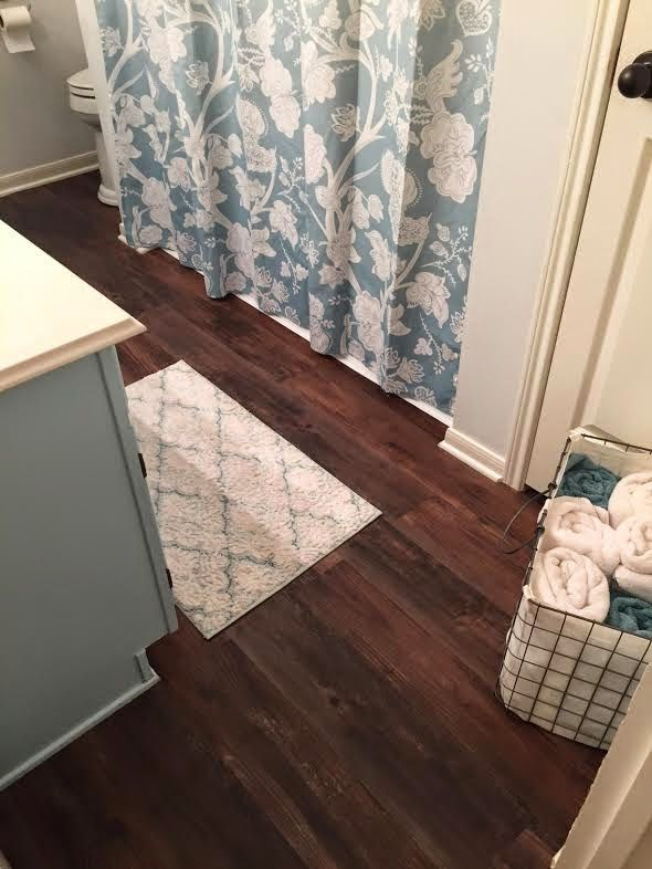 Ugly vinyl floor covered with wood-like Antique Woodland Oak  (#399147) peel and stick tiles from Lowe's.