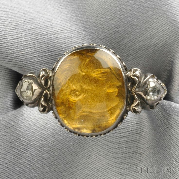 Fine Antique Commemorative Ring, 18th century, centering a gold depiction of a gentleman in profile under a buffed rock crystal dome, flanked by rose-cut diamonds, silver-topped gold mount, enamel gallery and shoulders.