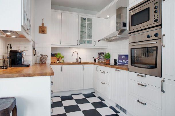 biała tradycyjna kuchnia skandynawska z drewnianymi blatami i czarnobiałą posadzką ułożoną w szachownicę