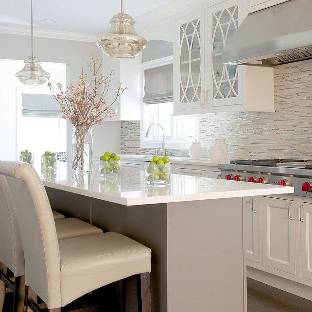 Caesarstone Frosty Carrina. Light grey island with cream color cabinets are balanced with the multi-color glass tiles. Soft hues of grey and cream are carried throughout the kitchen. #FrostyCarrina.