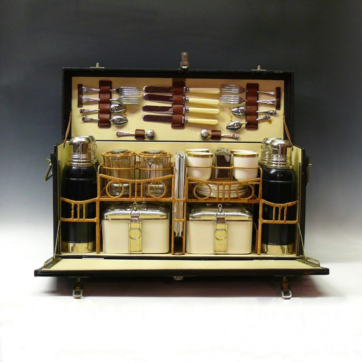 Bentleys — An wonderful vintage picnic hamper made by Coracle for Abercrombie & Fitch. Circa 1930. The set comprises: knives and forks for four people, teaspoons for four people, two cruet spoons, four thermos flasks, four drinks glasses, four enamelled plates, four cups and saucers, two ceramic food boxes with plated lids, one plated tea and sugar box, one ceramic butter jar, one ceramic preserve jar, one glass salt pot, one glass pepper or mustard pot.