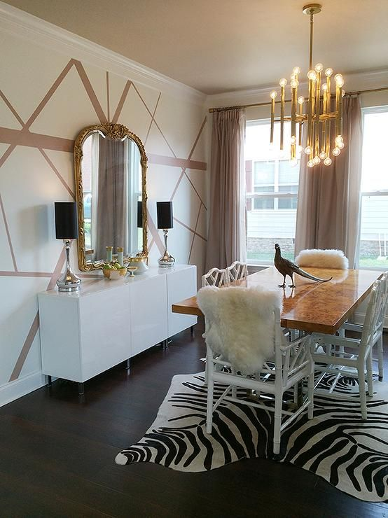 Fabulous dining room features a Jonathan Adler Meurice Chandelier illuminating a stainless steel and burl wood dining table, Bond Dining Table, lined with white bamboo dining chairs atop a black and white zebra cowhide rug.