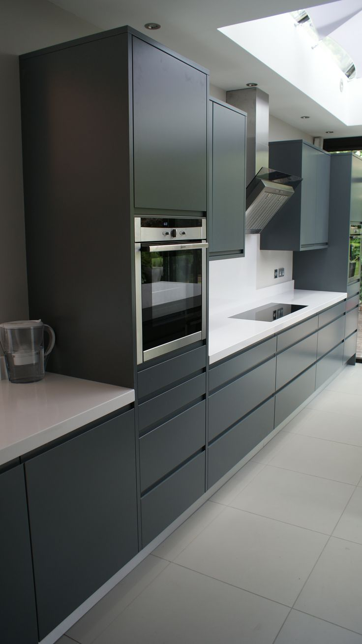 Modern handle-less grey matt painted bespoke kitchen with white Silestone tops in Kingston Surrey. Designed & fitted by Orchardkitchens.com of Egham