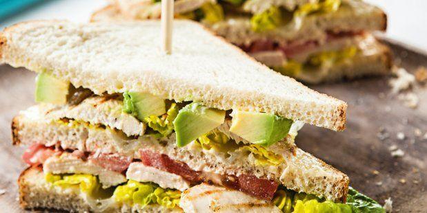 Club sandwich met gegrilde kipfilet, avocado, bacon, tomaat, romaine sla en mayonaise.