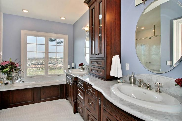Elegant wood cabinetry with a white marble countertop provides abundant storage space in this traditional bathroom. A window next to the tub offers a spectacular view of San Diego.