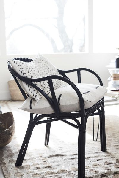 A detail of a black wicker chair with minimalist pillows.