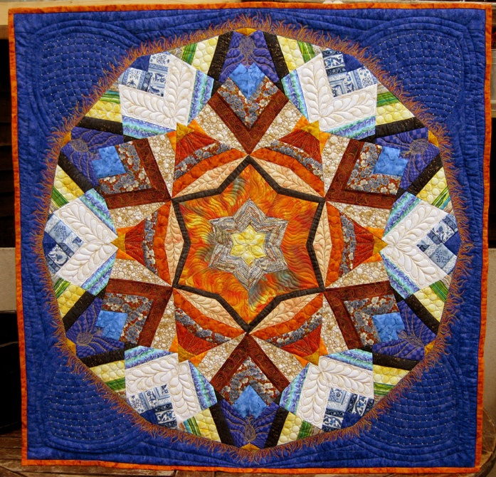 Kaleidoscope wallhanging pieced and quilted, the outer borders quilted with special rulers to have a cathedral window effect, and beaded in each  intersection.