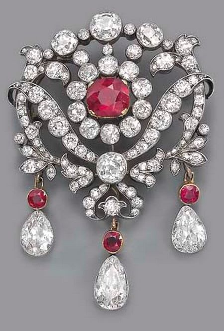 AN ANTIQUE RUBY AND DIAMOND BROOCH  The central cushion-shaped ruby and old-cut diamond cluster to the openwork diamond floral surround, suspending three detachable pear-shaped diamond and ruby drops, mounted in silver and gold, circa 1880