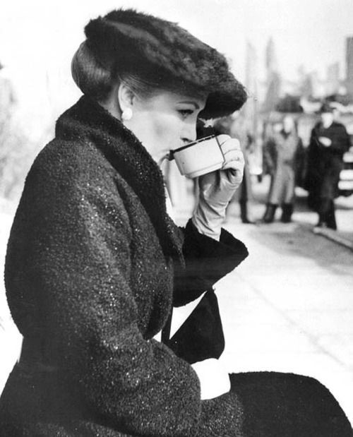 lovely image captured of a woman savoring a hot cup of coffee/tea?
