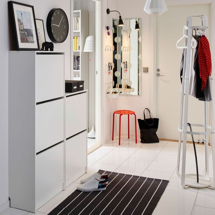 A whte hallway with white shoe cabinets on the wall combined with a hat/coat stand.