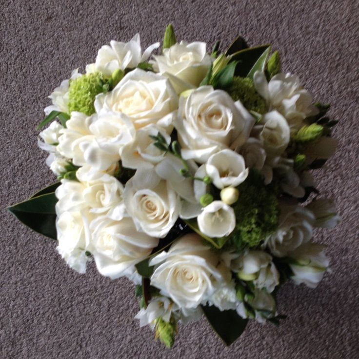Brides bouquet. Green and white roses, snowball tree, freesias, alstroemerias, and filler flowers.