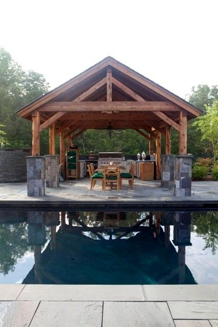 Same pool yard with a post and beam open-air outdoor kitchen.