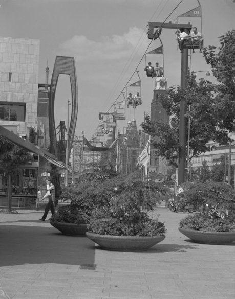 Kabelbaan boven de coolsingel in verband met de manifestatie C70 met links de bijenkorf om de hoek van de oldenbarneveldstraat, rechts op de achtergrond de stadhuis, 1970