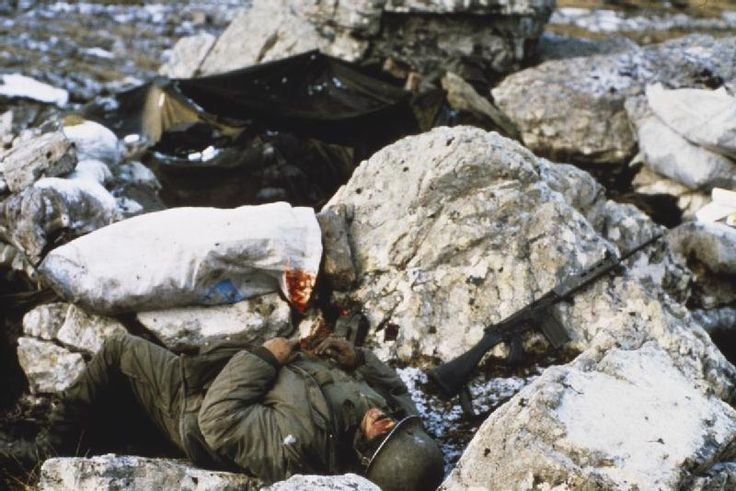 Falklands War, April-June 1982: A dead Argentine soldier, possibly of Regimento de Infanteria 4 (4th Infantry Regiment), on Mount Harriet, near Port Stanley. B and C Companies of this regiment defended Mount Harriet on the night of 11 - 12 June 1982 and suffered 23 casualties. Note the KIA's FN-FAL 7.62mm battle rifle lying on the rock next to him.