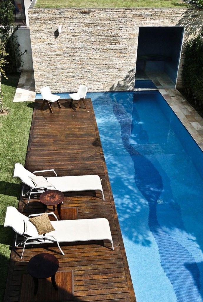 Piscinas pequenas  com deck de madeira e cadeiras, em área externa gramada