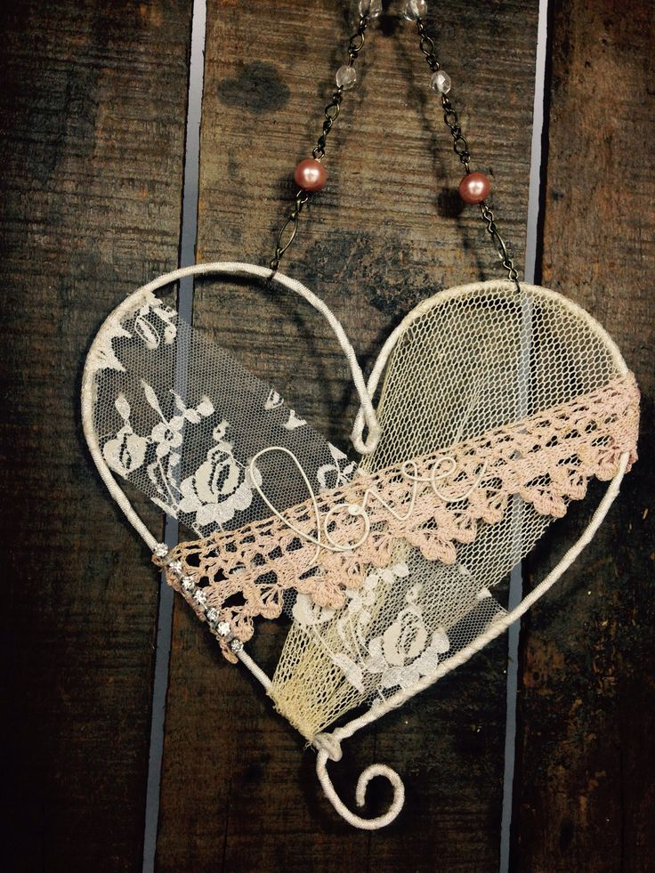 "This wire heart is about 7"" wide by 7"" tall with a chain embellished with pearls and crystals. Vintage lace and crochet edging are applied and sewn into place along with the word ""love"" formed out of                                                                                                                                                       More"