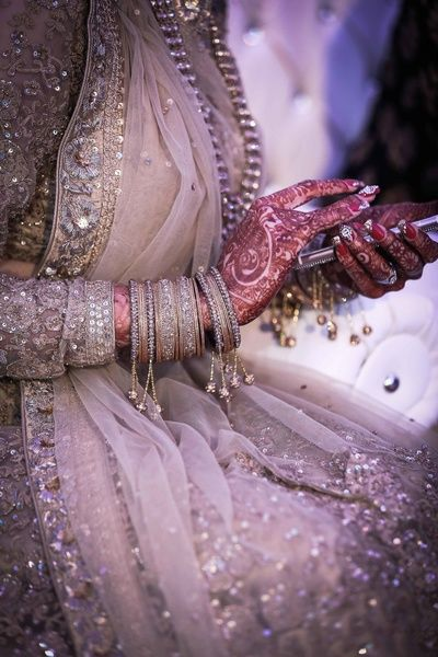 Bridal Details - Beige Sequinned Wedding Lehenga | WedMeGood | Gold and Silver Bangles with Hanging Ghungroos, Bridal Mehendi #wedmegood #bangles #bridaldetails #indianbride #indianwedding #ghungroo #mehendi #mehandi #bridal