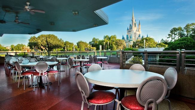 An outdoor dining area at Tomorrowland Terrace overlooking some greenery around the outskirts of Cinderella Castle