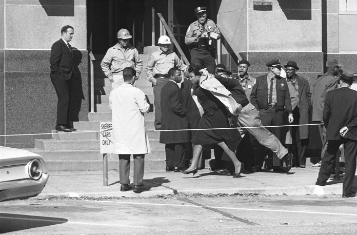 Amelia Boynton of Selma, is shoved along by her collar by Dallas County Sheriff Jim Clark following an argument which erupted as blacks lined up in front of the courthouse seeking to register to vote in Montgomery, Alabama, Jan. 19, 1965. Photo: Horace Cort, AP / 1965 AP
