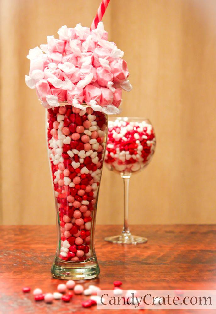 Centro de mesa de San valentín hecho con un vaso de cerveza, relleno de caramelos y como adorno una esfera de dulces con pitillo.