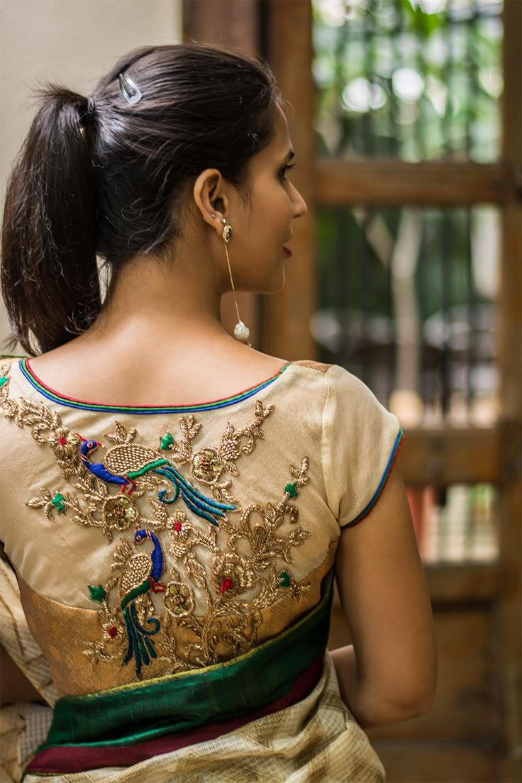 Rich and filled with details! A polka dotted goldish brocade bustier cut blouse with sheer sleeves and a striking back having a zardosi appliqué. Added detail magic in the form of multi coloured piping makes this one versatile blouse.   Pair with any saree having red, blue or green details and own that event!