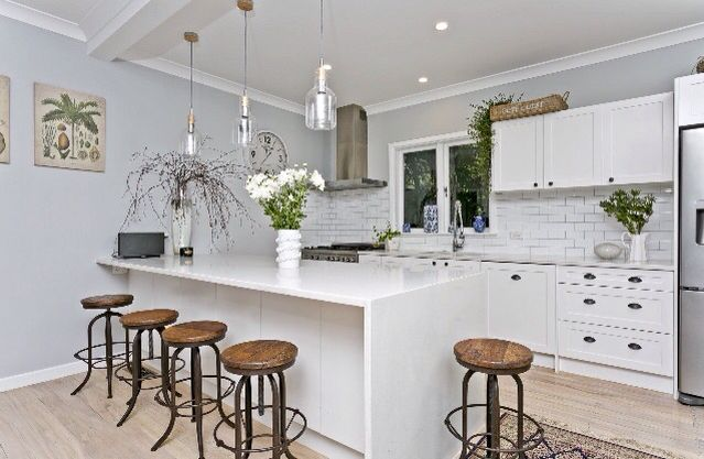 Wrought iron and wooden bar stools are strong pieces to anchor a home that uses a predominant white and grey style palate