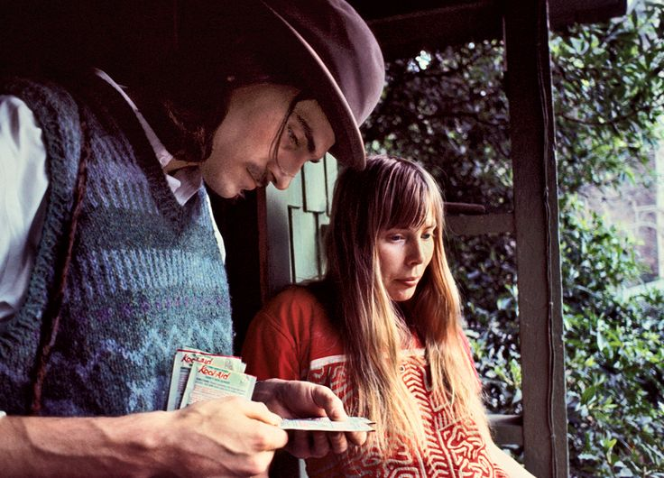 At Joni Mitchell's cottage on Lookout Mountain: James Taylor reading a Kool-Aid packet with Mitchell on the porch, January 1971.