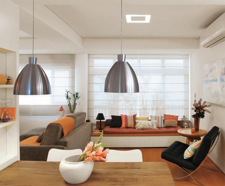 Sob a janela que vai quase até o chão, um móvel baixo serve como sofá e também como cama de hóspedes.