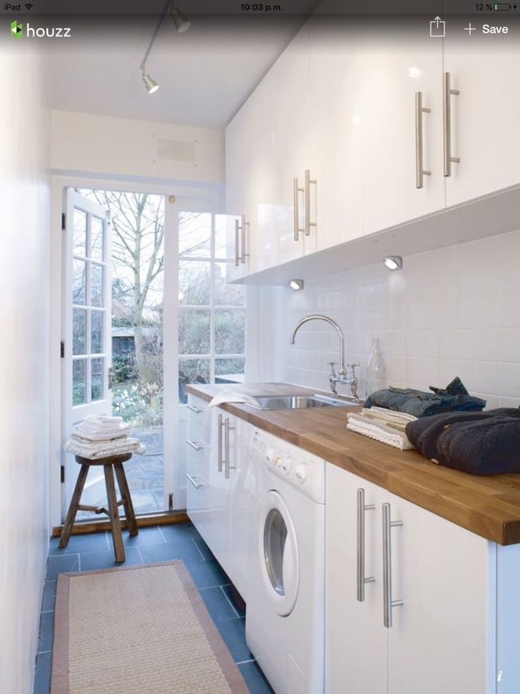 White narrow small laundry room with wood bench top and blue floor tiles. Overhead lights.