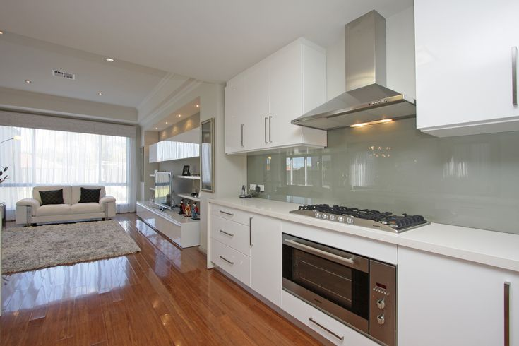 White Kitchen - light grey glasssplashback or mirrored splashback and timber floors or wood look tiles in a warm wood finish