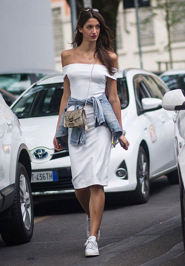 Look estiloso com vestido ombro a ombro, jaqueta jeans amarrada na cintura e tênis branco