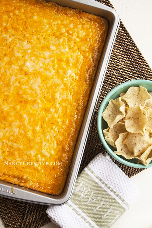 TEXAS TRASH WARM BEAN DIP by NancyC, adapted from Food.com Makes a 9 x 13″ pan  1 (8-ounce) package cream cheese, softened 1 cup sour cream 1 (4-ounce) can chopped green chiles, drained 2 (16-ounce) cans refried beans 1 (1-ounce) package taco seasoning mix 2 cups shredded Sharp Cheddar Cheese, divided 2 cups shredded Monterey Jack Cheese, divided