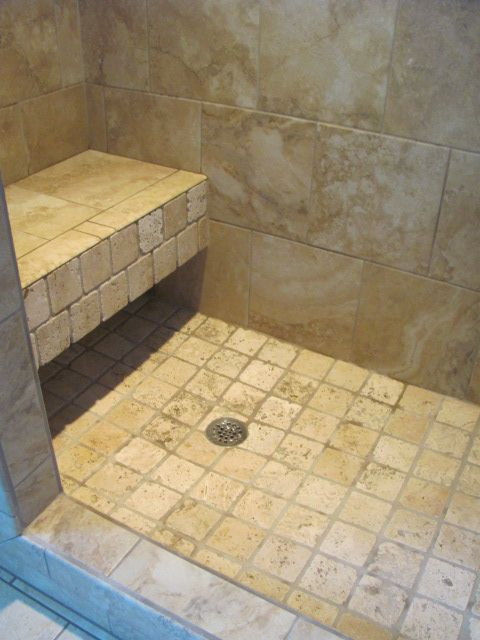 floating bench seat in a shower travertine facing and shower floor with a travertine style
