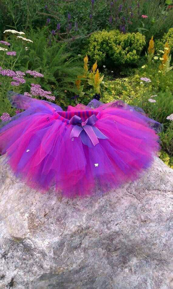 With a pink and purple striped tutu and cat ears (pink or purple)