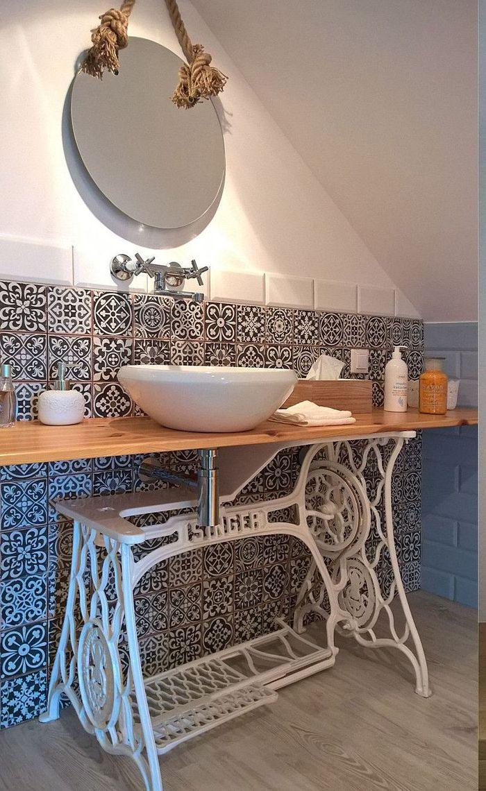 ancienne table de machine a coudre au pietement repeinte en blanc qui accueille une vasque a poser au design bol fabriquer un meuble de salle de bain