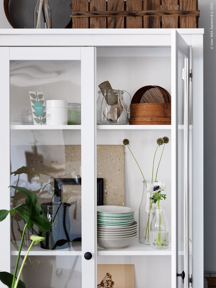 Naturtoner i HEMNES vitrinskåp i vitbets, ENSIDIG vaser, ENIGT skålar, DINERA djup tallrik i beige glaserat stengods.